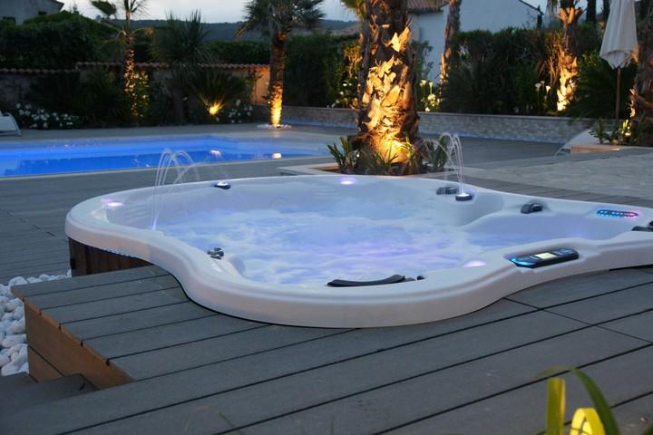 Amore Bay hot tub at dusk in a spacious backyard.